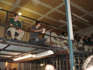 Corpsmembers view the talent show from the warehouse mezzanine.