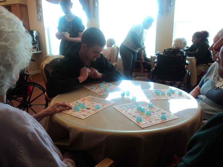 Vincent helps seniors fill in their cards during a game of food jingo